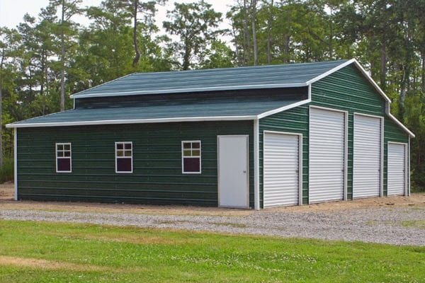 A green metal building with garage doors and windows from Newmart Builders