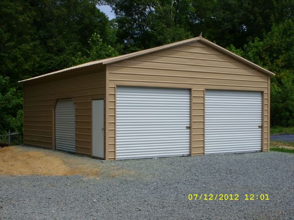 A Frame Garage with 2 rollup doors in the gable end, and a roll up door on the side with one walk in door Item #43